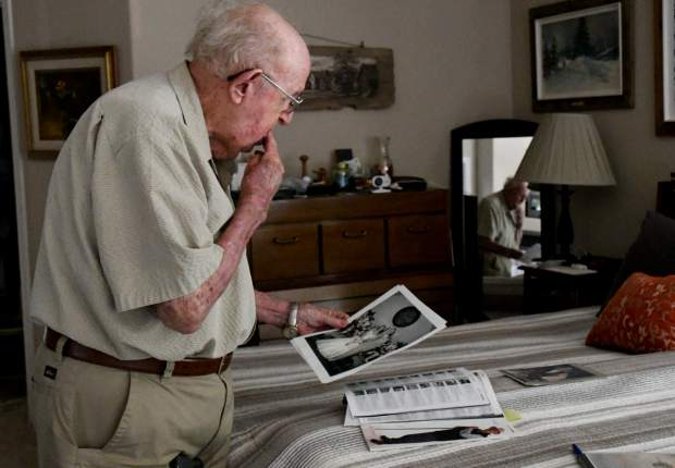 Carlton Hubbard looks at photos from his wedding day 65 years ago the week prior to his 90th birthday.