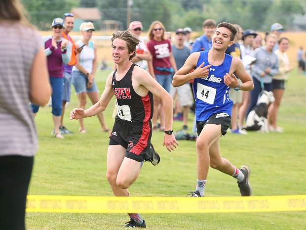 Aspen High School sophomore Brenon Reed, left, sprints to the finish of the Longhorn Invitational on Saturday, Aug. 24, 2019, at Crown Mountain Park. Reed finished 15th in 20:13.5. (Photo by Austin Colbert/The Aspen Times)
