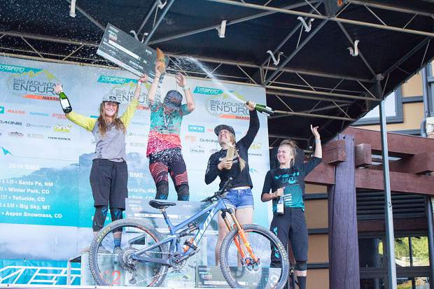 Stefanie McDaniel showers Cooper Ott and Lia Westermann on Sunday, Aug. 18, 2019, with champagne during the BME finals award ceremony in Snowmass Base Village. Lauren Bingham, right, placed fifth in the women's pro division for the whole BME race series, McDaniel placed third, Westermann placed second and Ott placed first. Zephyr Sylvester placed fourth overall but was not present at the awards ceremony.