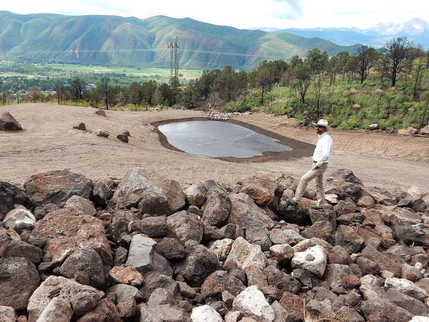 Basalt Town Manager Ryan Mahoney on Thursday surveys the catch basin created by Eagle County on the mountainside above the town. Grading directs water into boulder-lined channels which lead to the pond.