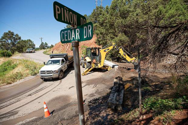 Town of Basalt employee Jeff Blevins uses a backhoe to remove flash flood debris from a basin on Monday at Pinon and Cedar Drive.