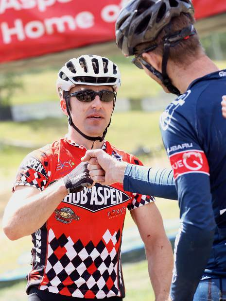 Aspen's Aaron Pool, left, gets a fist bump from race winner Thomas Herman of Lakewood after the Audi Power of Four 50-mile mountain bike race on Saturday, Aug. 17, 2019 in Snowmass. Pool finished third overall to lead the Roaring Fork Valley riders. (Photo by Austin Colbert/The Aspen Times)