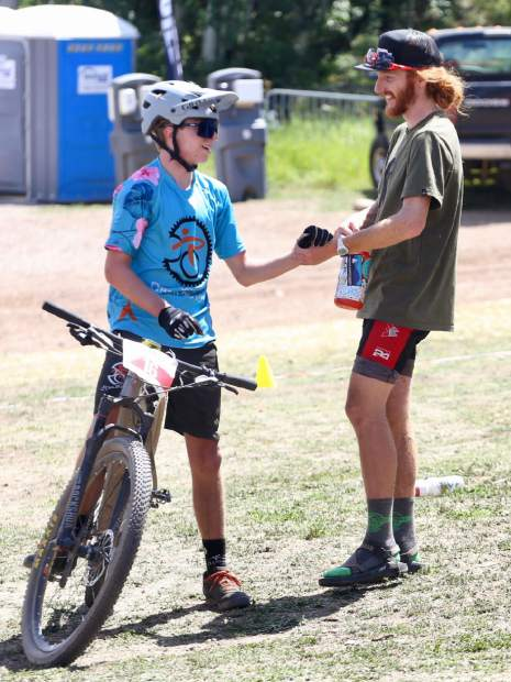 Runner-up finisher Cam Smith, right, chats with Aspen teen Caden Klein after the Audi Power of Four 50-mile mountain bike race on Saturday, Aug. 17, 2019 in Snowmass. Klein, 16, finished 13th overall. (Photo by Austin Colbert/The Aspen Times)