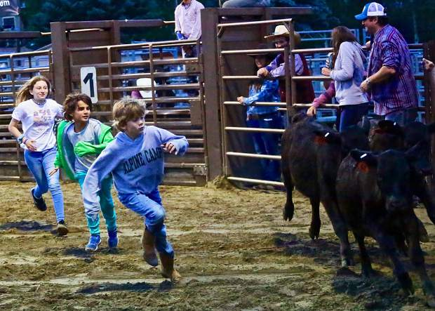 Kids chase down calves as part of a game during the Snowmass Rodeo on Wednesday, Aug. 7, 2019.