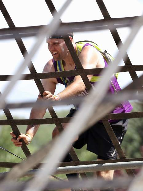 An athlete climbs the A-frame cargo net on Saturday, Aug. 3, 2019, during the first-ever Spartan obstacle-course race in Snowmass. (Photo by Austin Colbert/The Aspen Times)