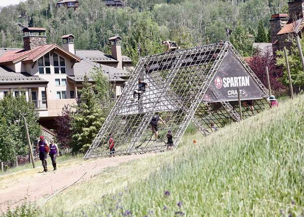 Athletes climb the A-frame cargo net on Saturday, Aug. 3, 2019, during the first-ever Spartan obstacle-course race in Snowmass. (Photo by Austin Colbert/The Aspen Times)