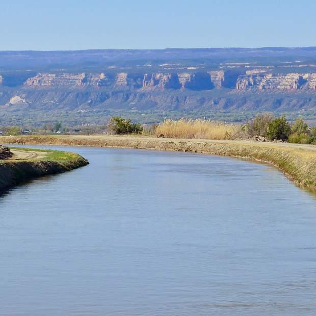 A large irrigation canal in the Grand Valley, which relies on water from the Colorado River to irrigate fields. The state is exploring how a voluntary, temporary and compensated water-use reduction plan, known as demand management, might work.