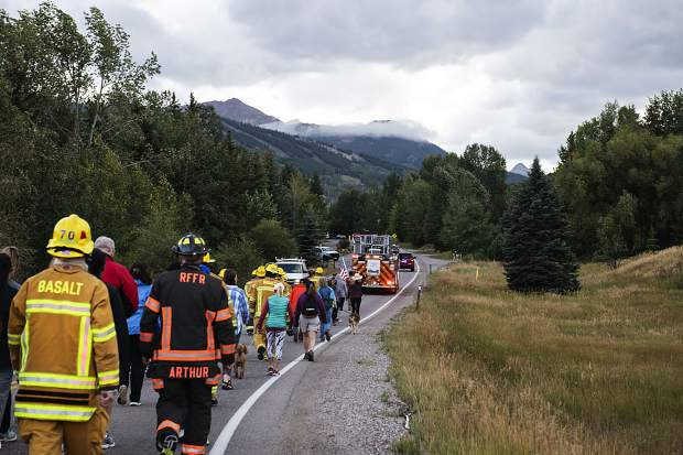 Firefighters and civilians participating in the Axes and Arms 9/11 March trek to the Top of the Village in Snowmass on Wednesday, September 11, 2019. (Kelsey Brunner/The Aspen Times)