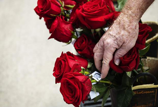 Tom Egan peeks through the photographs of fallen firefighters from the 9/11 terrorist attacks tied to red roses outside of the Aspen Fire Department on Wednesday, September 11, 2019. Egan's brother-in-law, Joe Marchbanks, was a battalion chief on 9/11 and was killed in the attacks. Battalion chief Marchbanks was running a command center in the South Tower when it fell. (Kelsey Brunner/The Aspen Times)