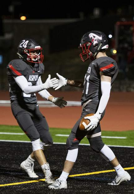 Aspen Skiers Aspen Skiers' Jonathon Woodrow (24), left, and Noah Akin (21) high-five after Akin's touchdown during the varsity game against Meeker High School in Aspen on Friday, September 13, 2019. (Kelsey Brunner/The Aspen Times)