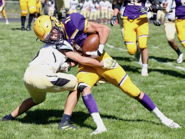 Basalt High School sophomore Gavin Webb lowers his shoulder against a Battle Mountain defender during their game on Saturday, Sept. 14, 2019, on the BHS field. The Longhorns won, 28-0. (Photo by Austin Colbert/The Aspen Times)