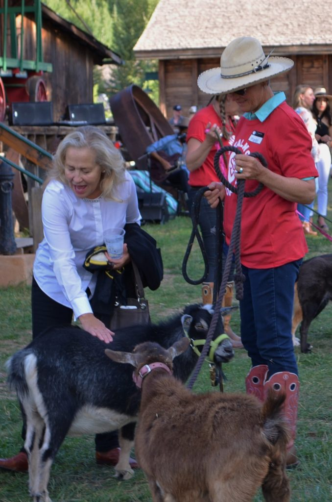 Claudia Cunningham, one of four testimonial speakers at the Hay Bale Ball, pets Lester the goat.