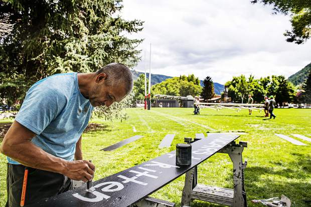 Freddy Waititi paints the name of a Rugby team on a plank fo wood for Ruggerfest at Wagner Park on Wednesday, September 18, 2019. The panels will be added into the scoreboard to keep track of the teams during the event. Waititi is a member of Aspen's Rugby Club and was donating his time to set up for the tournament. (Kelsey Brunner/The Aspen Times)