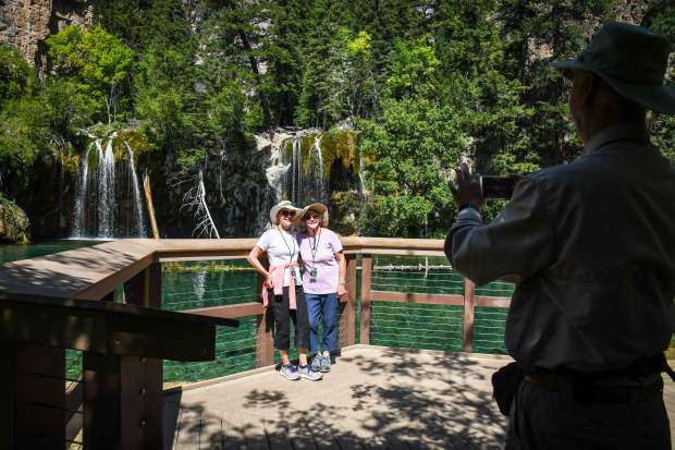 Friends Crane Anderson and Carolyn Mugge stand together while they get their photo taken with Hanging Lake in the background. The friends were visiting from Rhode Island and Denver and were celebrating finishing the difficult trail at the age of 70.