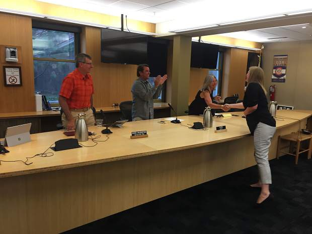 Aspen City Manager Sara Ott shakes hands with Councilwoman Ann Mullins as Mayor Torre and Councilman Ward Hauenstein look on. The council on Tuesday approved an employment contract making Ott city manager.