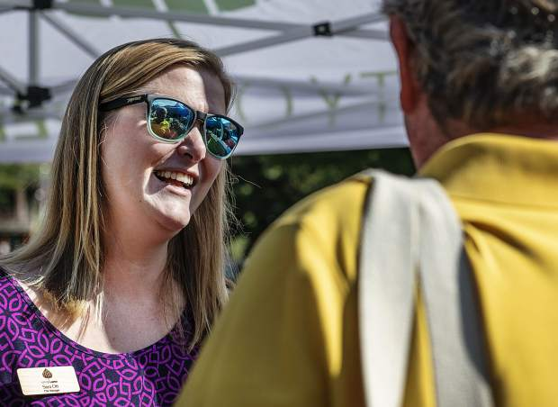 City Manager Sara Ott, left, talks to local Mark Rothman at the city of Aspen booth at the farmer's market on Saturday, September 7, 2019. (Kelsey Brunner/The Aspen Times)