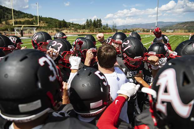 Aspen High School varsity football huddle before the start of the second half of the game against Bayfield High School on Saturday, September 7, 2019. (Kelsey Brunner/The Aspen Times)