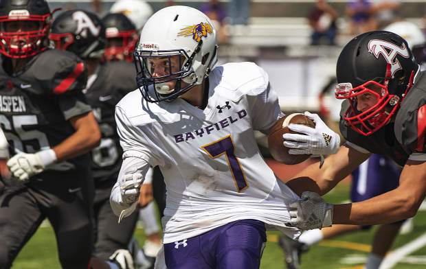 Bayfield's James Mottin runs the ball as Aspen players try to tackle him during the varsity game in Aspen on Saturday, September 7, 2019. (Kelsey Brunner/The Aspen Times)
