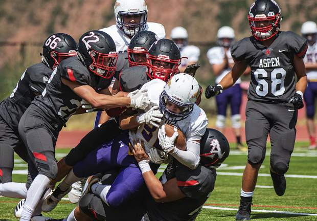 Bayfield's Cade Carlson is tackled by Aspen players during the varsity game in Aspen on Saturday, September 7, 2019. (Kelsey Brunner/The Aspen Times)