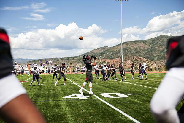 Aspen's Dillon Hendrickson reaches for a pass as his teammates watch him from the sidelines during the game against Bayfield High School on Saturday, September 7, 2019. (Kelsey Brunner/The Aspen Times)