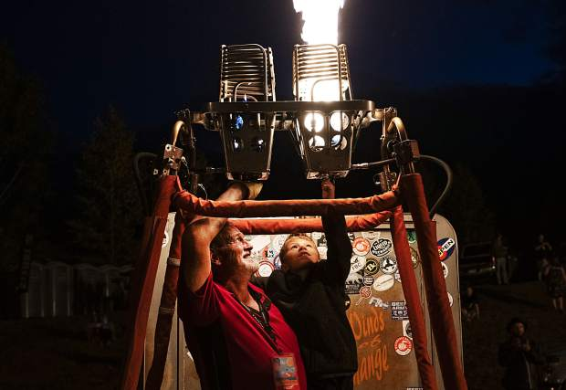 Kenny Bradley, left, holds Alex Broadhurst, 7, as he ignites the burners on Bradley's basket during the 44th Annual Snowmass Balloon Festival in Snowmass on Friday, September 6, 2019. The glow was cancelled due to weather, but the balloonists still entertained the crowds with candlesticking.