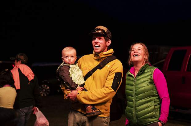 Dan Perl, center, holds son Ollie Perl, 18 mo., with mom Ashley Perl, right, as they watch the burners ignite during the 44th Annual Snowmass Balloon Festival in Snowmass on Friday, September 6, 2019.