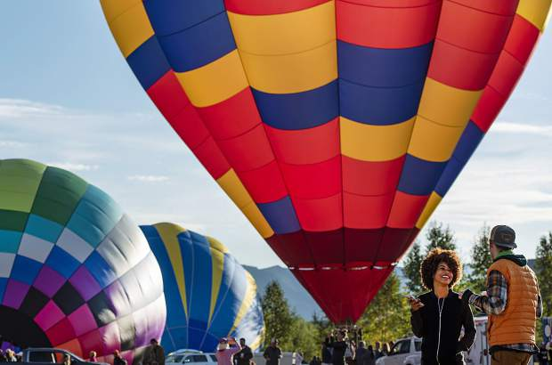 Beatriz Lopes, center right, and Dylan Brown, right, share a moment during the start of the 44th Annual Snowmass Balloon Festival in Snowmass on Friday, September 6, 2019. Brown is from Aspen, but currently lives in Brazil with Lopes. The two were in town for the weekend visiting.
