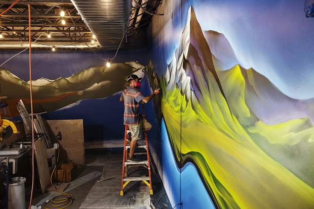 Chad Bolsinger adds details to his mural in the new Collective Snowmass in Base Village on Friday, September 13, 2019. Bolsinger is a muralist out of Denver and is working on a large-scale spray paint piece for the space expected to open for ski season. (Kelsey Brunner/The Aspen Times)