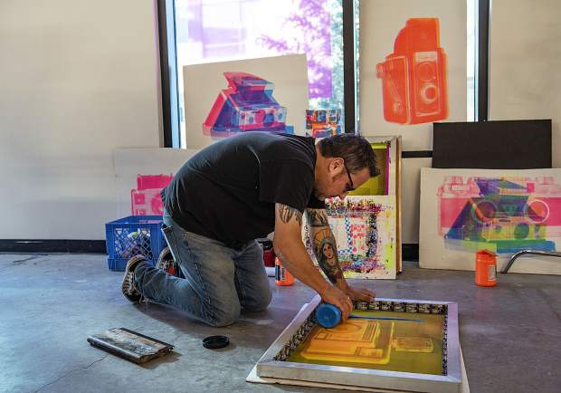 Photographer and screen printer John Johnston spreads blue paint to begin a practice piece of multiple layered paintings of cameras in The Collective on Friday, September 13, 2019. (Kelsey Brunner/The Aspen Times)