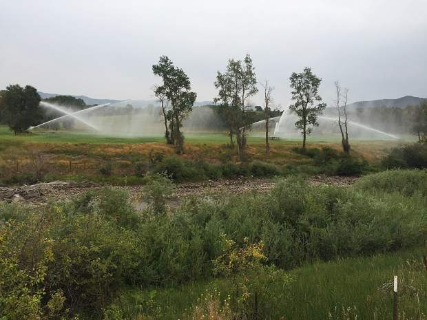Sprinklers irrigate land on the east side of the Crystal River (in foreground) in August 2018, one of its driest years in recent history. A call by a downstream senior water rights holder during the drought of 2018 illustrated a long-simmering problem: several subdivisions in the Crystal River Valley don't have backup water plans.