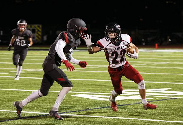 Grand Valley High School's Caleb Frink (22) fends off Aspen High School's Jack Seamans (6), left, during the homecoming game in Aspen on Friday, Sept. 27, 2019. (Kelsey Brunner/The Aspen Times)