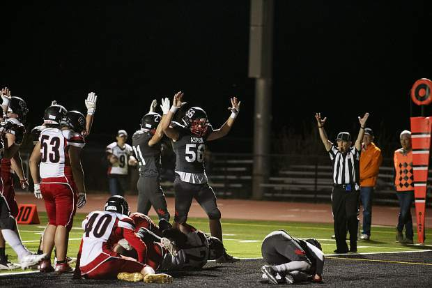 Aspen High School Skiers raise their hands to signal the touchdown scored by Jon Haisfield (12) during the homecoming game against Grand Valley High School in Aspen on Friday, Sept. 27, 2019. (Kelsey Brunner/The Aspen Times)