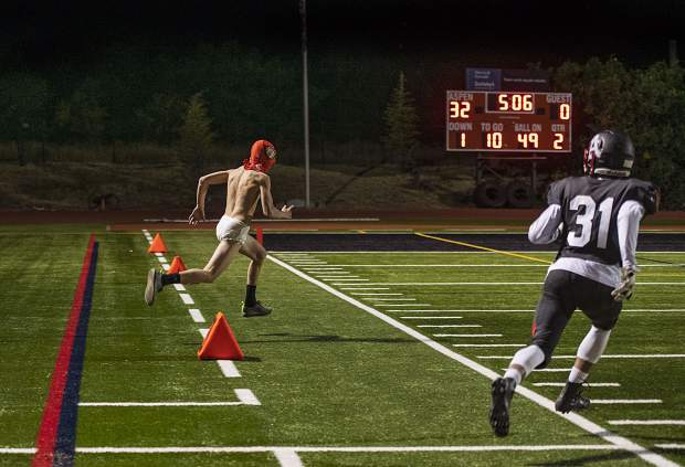 Aspen High School's Kiernon Smith, right, chases after a streaker during the second quarter of the homecoming game on Friday, Sept. 27, 2019. (Kelsey Brunner/The Aspen Times)