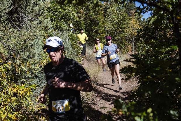 Runners turn a corner on the descent near mile 11 during the Golden Leaf Marathon on Saturday, September 28, 2019. (Kelsey Brunner/The Aspen Times)