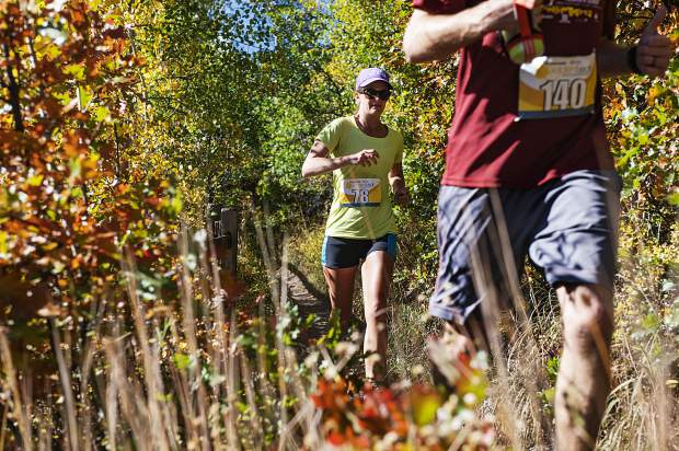 Amy Rollins, left, follows closely behind Scott Smith as they finish their descent after mile 11 near Tiehack ski area during the Golden Leaf Half Marathon on Saturday, September 28, 2019. (Kelsey Brunner/The Aspen Times)
