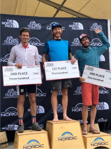 Gunnison's Cam Smith, center, stands on the Grand Traverse podium. Smith won both Saturday's foot race and the overall Triple Crown title.
