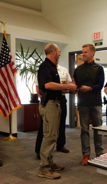 Scott Akin, right, thanks Snowmass Village Police Chief Brian Olson for his role in helping save Akin's life after he suffered cardiac arrest in January.