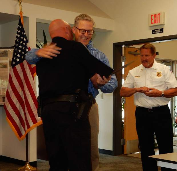 Scott Schwarting, middle, gives Basalt Police Officer Jason Hegberg a hug Sept. 17 during a ceremony honoring first responders for saving lives of three cardiac arrest victims this year. Hegberg performed CPR on Schwarting. Roaring Fork Fire Rescue Chief Scott Thoompson looks on.