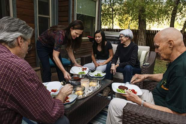 The Locke family prepares plates of a vegetarian dinner on their back porch in Basalt on Friday, Sept. 27, 2019. Karen and Kelly Locke are both family physicians. (Kelsey Brunner/The Aspen Times)