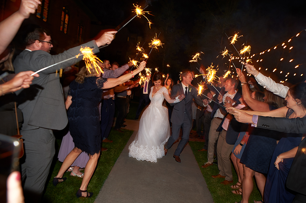 Mr. and Mrs. Kaptuska depart their reception through a tunnel of sparklers.