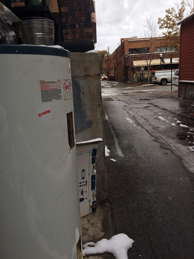 An abandoned water heater placed in an alley next to the door of Aspen Mayor Torre's apartment is one of hundreds of items that will be removed by the city on Thursday as part of a daylong clean up effort.