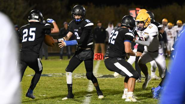 Coal Ridge Titan quartback Karson DuBois hands the ball off to Kobe Wild during Friday night's game against the Basalt Longhorns.