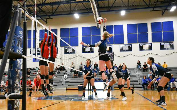 Coal Ridge Titan Phoebe Young jumps to spike the ball over the net towards the defending Aspen Skiers during Tuesday night's game at Coal Ridge High School.