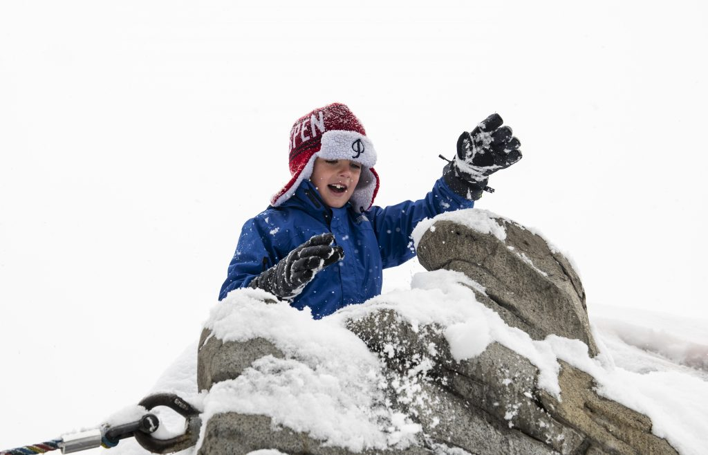 Thor Gleasman, 6, pushes snow from the top of the playground next to Wagner Park on Thursday, October 10, 2019.