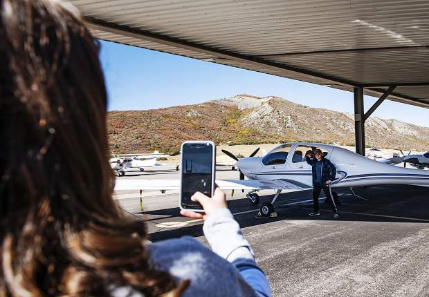 Bennett Jones, 14, left, takes a photo of Hayden Murray of Snowmass, 14, while he poses in front of the plane he's going to be flying in at the Aspen/Pitkin County Airport on Thursday, October 3, 2019. (Kelsey Brunner/The Aspen Times)