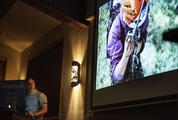 Mike Libecki looks at the film from one of his many expeditions during The Longevity Project event in the Mountain Chalet on Tuesday, October 1, 2019. (Kelsey Brunner/The Aspen Times)
