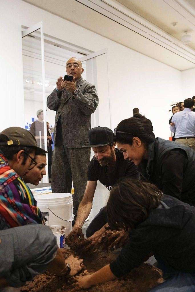 Abraham Cruzvillegas takes photos on his phone of the attendees interacting with his exhibit at the Aspen Art Museum on Thursday, October 17, 2019. (Kelsey Brunner/The Aspen Times)