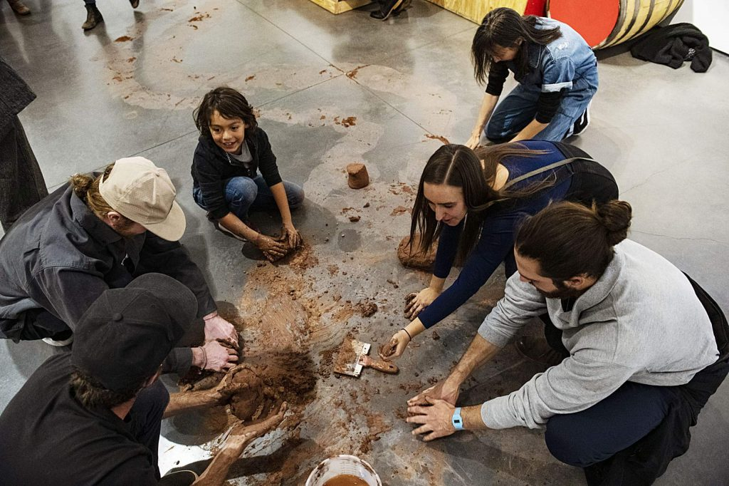 Attendees of the Abraham Cruzvillegas exhibition create with clay on the floor of the Aspen Art Museum on Thursday, October 17, 2019. (Kelsey Brunner/The Aspen Times)