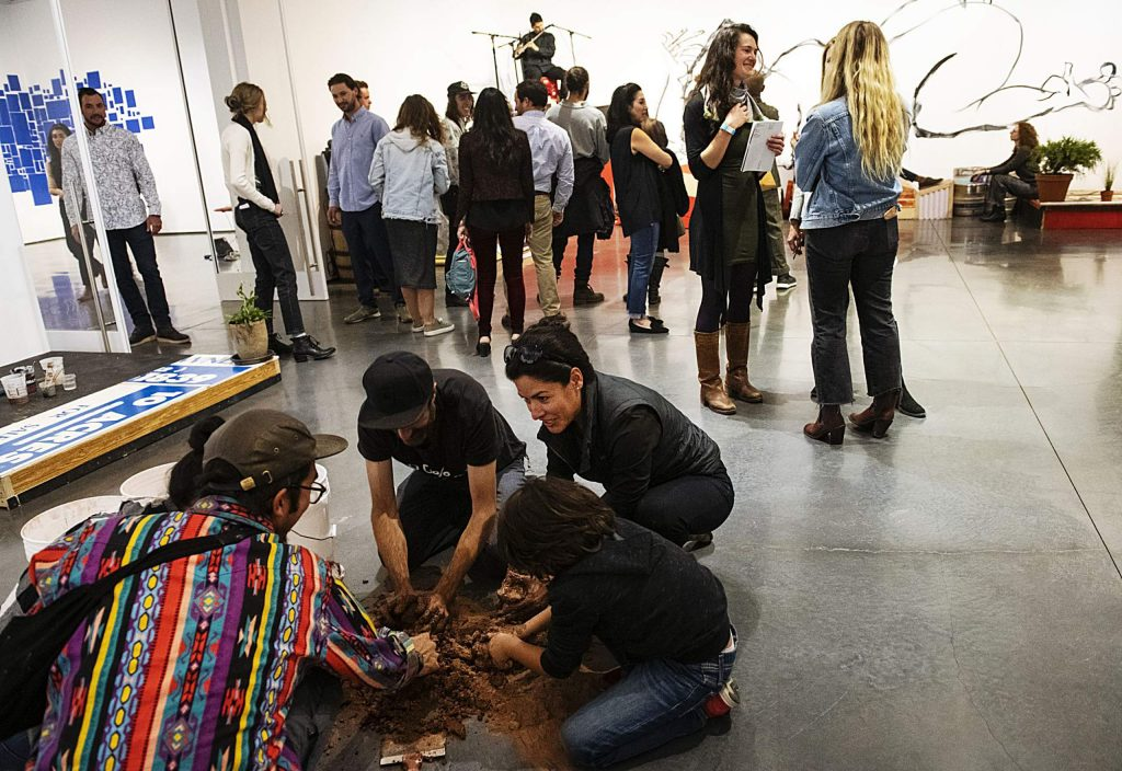 Attendees of the Abraham Cruzvillegas exhibition mix clay on the floor of the Aspen Art Museum on Thursday, October 17, 2019. (Kelsey Brunner/The Aspen Times)