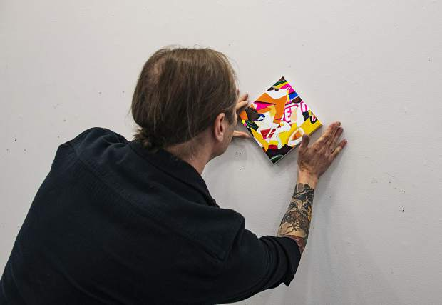Robert Brinker displays one of his small canvas paintings as he plans to hang them in his upcoming show at the Art Base in his studio on Wednesday, October 9, 2019. (Kelsey Brunner/The Aspen Times)
